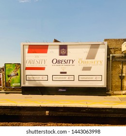 Chelmsford, UK - 5 July 2019: Obesity causes cancer too. Cigarette style health warning on a billboard at the train station.