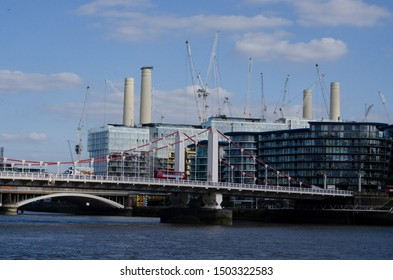 chelsea iron made bridge sustains over the thames river in london taken august 22 2019 seen background skycrapers and battersea power station where red iconic london buses crosses to Battersea