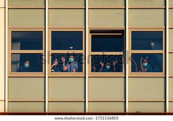 Chelsea, London / UK - May 14 2020: NHS key workers wave from windows of Chelsea and Westminster Hospital at 8pm as crowds cheer NHS workers during Coronavirus COVID-19 outbreak