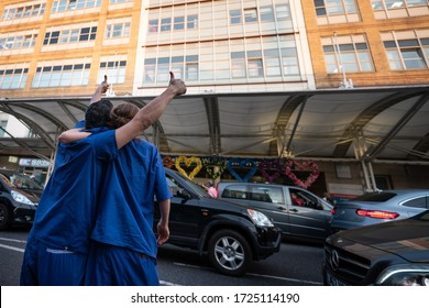 Chelsea, London / UK - May 7 2020: NHS key workers hug and look up at colleagues in Chelsea and Westminster Hospital at 8pm as crowds cheer NHS workers during Coronavirus COVID-19 outbreak