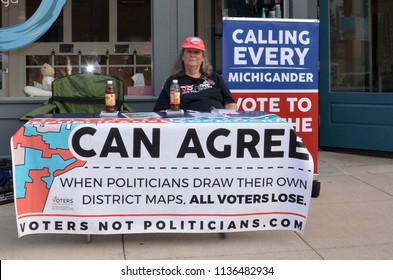 CHELSEA, MI / USA - JULY 12, 2018:  A woman staffs a booth supporting the group Voters not Politicians at the Chelsea Sounds and Sights on Thursday Nights festival.