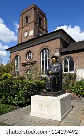 Chelsea Old Church (or All Saints) with Sir Thomas More statue in London.