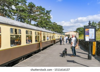 CHELTENHAM, ENGLAND - SEPTEMBER 2019: People on the platform of Cheltenham Racecourse Station on the Gloucestershire and Warwickshire Steam Railway. A train is in the station.