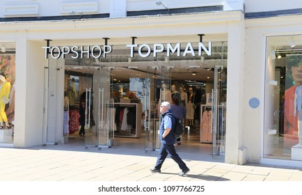 Cheltenham, Gloucestershire, England,   UK. 14 May 2018.  The front entrance of a Topshop Topman store with passing shopper.