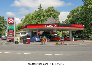 Cheltenham Gloucestershire UK 15th JULY 2019 Texaco Garage Petrol Station showing petrol and diesel prices with young woman filling up her car