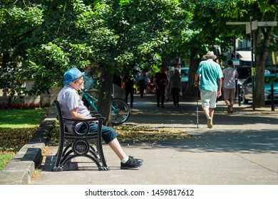 Cheltenham Gloucestershire UK 23rd JULY 2019 An old man sitting on a bench on a hot summers day, smoking his pipe on Cheltenham Promenade