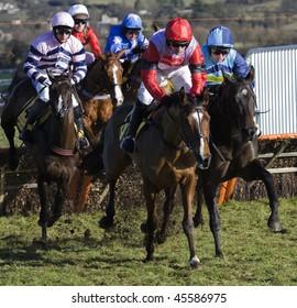 CHELTENHAM, GLOUCS; JAN 30:  Jockeys battle over hurdles in the first race at Cheltenham Racecourse, UK, January 30, 2010 in Cheltenham, Gloucestershire