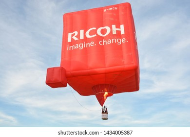 Cheltenham, United Kingdom. June 22, 2019 - Big red, square hot air balloon in the sky.