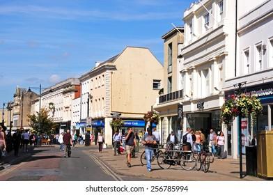 CHELTENHAM, UNITED KINGDOM - SEPTEMBER 8, 2014 - Shops with shoppers and tourists along the High Street, Cheltenham, Gloucestershire, England, UK, Western Europe, September 8, 2014.