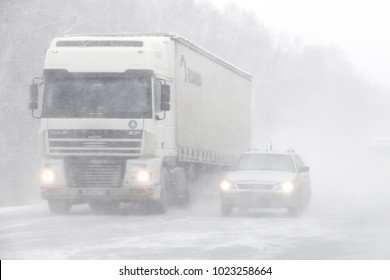 Chelyabinsk region, Russia - February 10, 2018: Semi-trailer truck DAF XF and motor car Lada Priora at the interurban road during a heavy blizzard.