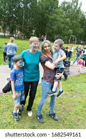 Chelyabinsk Region, Russia - JULY 2019. Grandmother and mother with children at the festival of colors. Holiday in the province with the participation of many nations, music, dance, entertainment for