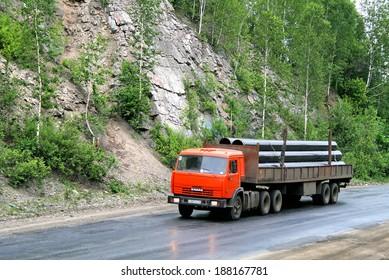 CHELYABINSK REGION, RUSSIA - JUNE 29, 2008: Orange KAMAZ 54115 semi-trailer truck at the interurban road.