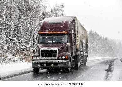 CHELYABINSK REGION, RUSSIA - OCTOBER 11, 2015: Semi-trailer truck Freightliner Century Class at the interurban freeway during a heavy snowfall.