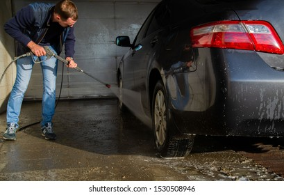 Chelyabinsk Region, Russia - October 2019. A man washes a car under high pressure.