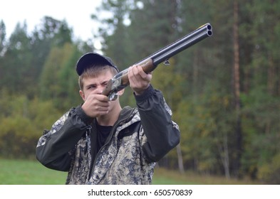 Chelyabinsk Region, Russia - September 17, 2016: A hunter in a camouflage shoots a gun. Hunter in the forest of autumn taking aim in the bird.