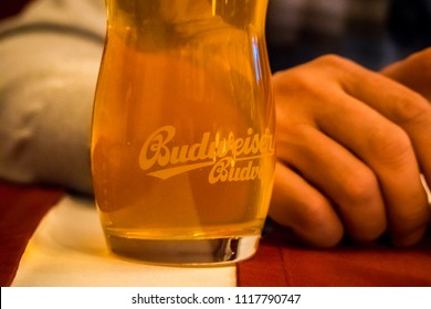 CHELYABINSK, RUSSIA - 20 June 2018: A person sitting at a bar enjoying a Budweiser beer. Original glass of Budweiser Beer. An American lager first introduced in 1876.