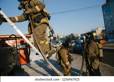 CHELYABINSK, RUSSIA, December 11, 2018:  Firefighters climb the stairs of the fire truck on the roof of the building. MCHS rescuers on fire extinguishing exercises