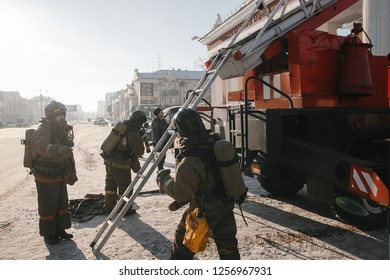 CHELYABINSK, RUSSIA, December 11, 2018: Group of firefighters advance forward putting out a fire. Firefighters prepare to climb the burning building. MCHS rescuers on fire extinguishing exercises.
