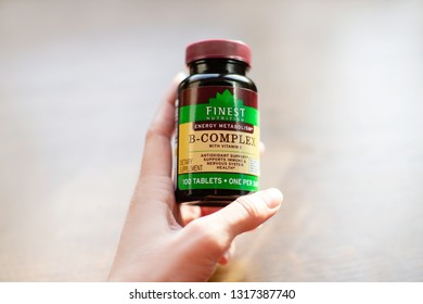 Chelyabinsk, Russia - February 15, 2019: Female hand hold Finest Nutrition B-complex - product by Walgreens