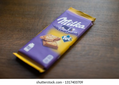 Chelyabinsk, Russia - February 15, 2019: Milka chocolate bar with Tuc cracker with wooden background. Milka is a brand of chocolate confection by Mondelēz International (Kraft Foods)