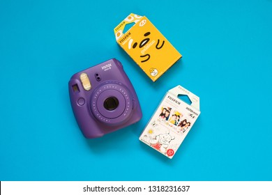 Chelyabinsk, Russia - February 15, 2019: Fujifilm instax mini camera and gudetama and Winnie the Pooh instant film on blue background