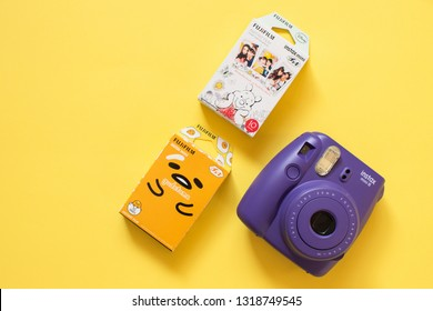 Chelyabinsk, Russia - February 15, 2019: Fujifilm instax mini camera and gudetama and Winnie the Pooh instant film on yellow background