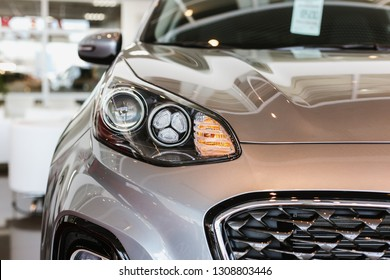 Chelyabinsk, Russia - February, 6 2019: Cars in the Kia showroom. Car headlights on gray auto and radiator grille