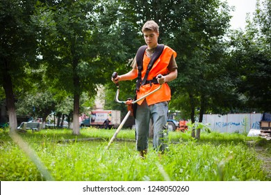 Chelyabinsk Russia - July 29, 2014: A young guy in an orange vest mows the grass in the yard on Engels street