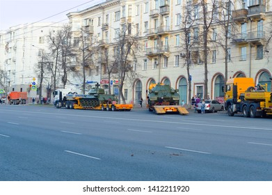 Chelyabinsk, Russia - May 2019: Transportation of heavy armored vehicles along Lenin Avenue. T-34-85 stands on the trawl, the IS-2 mechanic secures the hitch. Parade rehearsal
