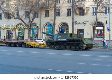 Chelyabinsk, Russia - May 2019: Transportation of heavy armored vehicles along Lenin Avenue. ISU-152 is on asphalt and is preparing to climb the trawl along the gangways