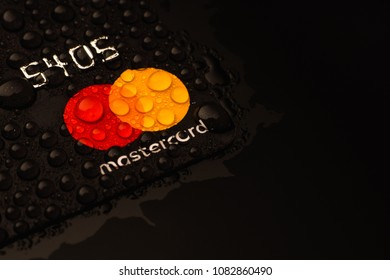 CHELYABINSK, RUSSIA - NOVEMBER 10,2017. Bank credit card Master Card Black macro, close-up. Concept card on a water drop. Black background. Shallow depth of field.