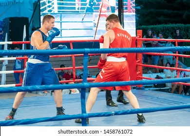 """Chelyabinsk, Russian Federation - 22 July 2019, Boxing, a Boxing match between two blue and red boxers. Demonstration Boxing fight at the festival """"international Boxing Day""""."""