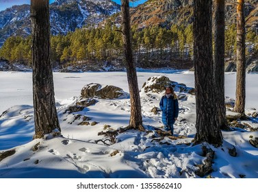 Chemal / Russia - Feb 2019: The girl on the trail in the forest over the frozen Katun river in Altai Mountains near Chemal village. Russian winter in Siberia.