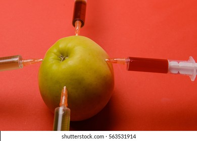 Chemical additives in food or genetically modified fruit concept. Green apple with syringes of chemicals. Isolated on red background.