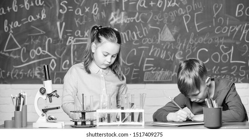 Chemical analysis. Kids busy study chemistry. School chemistry lesson. School laboratory. Girl and boy smart students conduct school experiment. Describe chemical reaction notepad. School education.