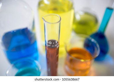 chemical bottles and graduated tube filled with colored liquids, focus select