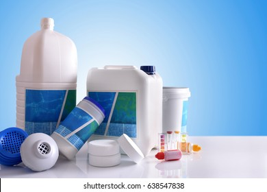 Chemical cleaning products for pool water on white table and blue background. Horizontal composition. Front view