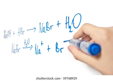chemical equation written on whiteboard with hand holding marker