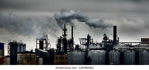 Chemical factory on a hazy day; silos, factory pipe, smoke