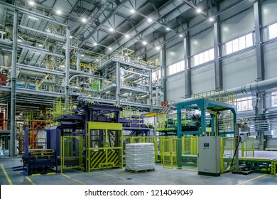 Chemical factory. Thermoplastic production line. Production and packing machinery in large area of industrial hall.