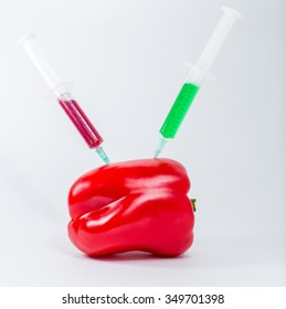 Chemical fertilizer for growing vegetables and . Bulgarian red pepper in syringes with different colored chemicals.