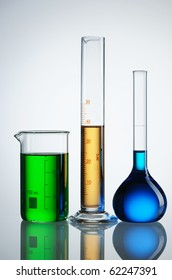 Chemical flasks with reagents over white - green, yellow and blue