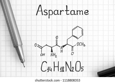 Chemical formula of Aspartame with black pen. Close-up.