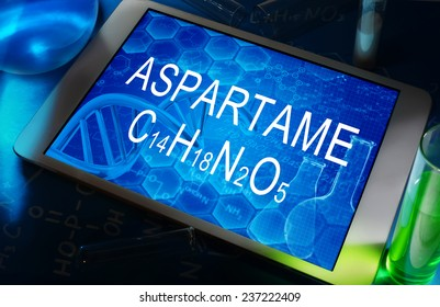 the chemical formula of aspartame on a tablet with test tubes