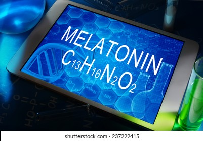 the chemical formula of melatonin on a tablet with test tubes