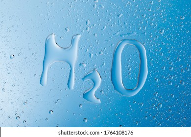 Chemical formula of water. water letters of H2O on blue wet background.