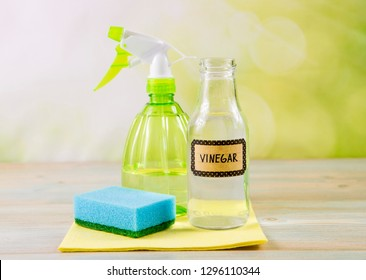 Chemical free home cleaner products concept. Using natural destilled white vinegar in spray bottle to remove stains. Tools on wooden table, green bokeh background, copy space.