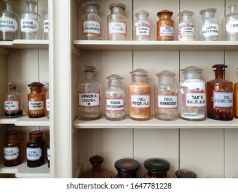 Chemical ingredients in glass bottles, labeled in Latin script, standing on shelves in old historic pharmacy
