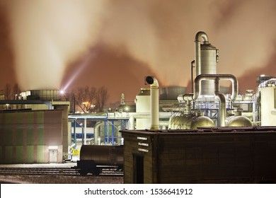 Chemical plant detail with a lot of steam illuminated by a spotlight.