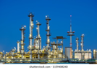 A chemical plant at with night blue sky, a telecommunications tower in the background.
